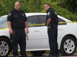 St. John the Baptist Parish Sheriff deputies examine a car with bullet holes at a crime scene where two sheriffs were killed and two wounded in an early morning shootout on Aug. 16.
