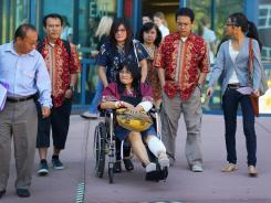 "Rita Paulina, who was wounded during the shooting at ""The Dark Knight Rises,"" leaves in a wheelchair with her family from the Arapahoe County Courthouse after attending an arraignment hearing for suspect James Holmes on July 30."