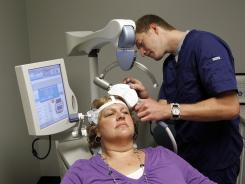 Brenda Rylchoek receives a treatment from a Transcranial Magnetic Stimulation device at the office of Dr. Charles Wadle in West Des Moines, Iowa on Thursday.