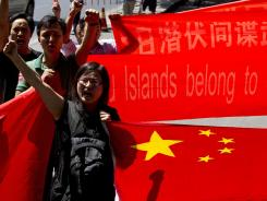 Anti-Japan protesters shout slogans while marching outside Japanese Embassy with Chinese national flags and banners Sunday in Beijing.