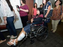 Rita Paulina, injured in the Colorado movie theater shooting, arrives in a wheelchair at the Arapahoe County Courthouse for the arraignment of accused gunman James Holmes on July 30.