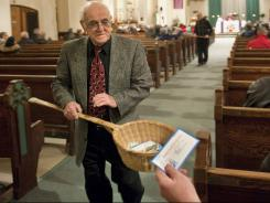John Alves uses a basket to take collections during Mass at St. John the Baptist Roman Catholic Church in New Bedford, Mass., Dec. 19, 2009.