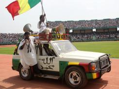 A car with national flag rides as people gather in Bamako for a giant peace rally in Mali, which was split in two after Islamists wrested control of the vast desert north following a March coup in the capital.
