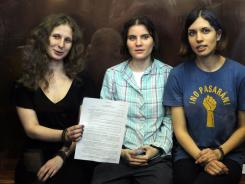 Feminist punk group Pussy Riot members, from left, Maria Alekhina, Yekaterina Samutsevich, and Nadezhda Tolokonnikova show the court's verdict as they sit in a glass cage at a courtroom in Moscow.