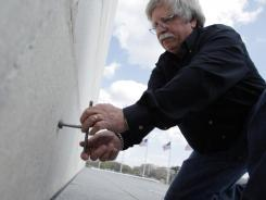 In this March 13 photo, David Doyle of the National Oceanic and Atmospheric Administration (NOAA) National Geodetic Survey, turns a steel rod used for surveying at the base of the Washington Monument.