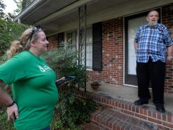 George Hansen, 74, talks with Americans for Prosperity volunteer Amy Bryson, 30, in Garner, N.C., on Aug. 14.