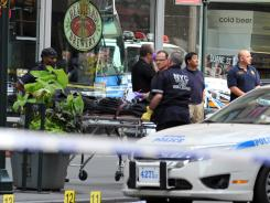 Investigators remove the body of the alleged shooter near the Empire State Building Friday. A disgruntled former employee at a women's apparel shop shot a former co-worker before being killed by police.