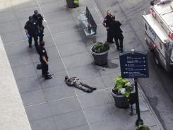 New York City police approach the lifeless body of Jeffrey Johnson. Police say Johnson, who was laid off from a nearby shop in 2011, shot and killed a former colleague near the Empire State Building.