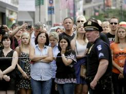 Bystanders and a police officer stand on Fifth Avenue to view the scene after a multiple shooting Friday outside the Empire State Building.