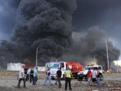 Firefighters and rescue teams work at the Amuay oil refinery after an explosion in Punto Fijo, Venezuela, on Saturday.