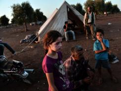 A Free Syria Army fighter sits with his children at an unofficial rebel camp set up near the Syrian-Turkish border on Monday.