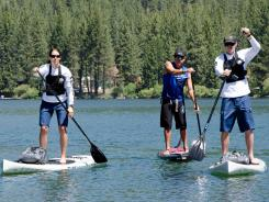 From left, officer Lisa Madden; Ronnie Ayres, a former ocean lifeguard and marine safety officer who instructed the team on paddling technique, board maneuvering, safety and lifesaving skills; and officer Chase Covington patrol Donner Lake in Truckee, Calif.