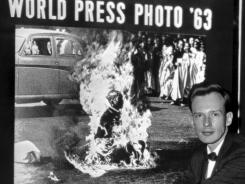 In this Dec. 14, 1963, photo, Malcolm Browne, Saigon correspondent for the Associated Press, poses in front of his photo of a Vietnamese Buddhist monk's fiery suicide.