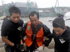 A Chinese fisherman, center, is rescued by South Korean coast guard officers Tuesday in Jeju, South Korea.