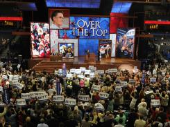 Delegates wave signs as Mitt Romney receives enough votes to secure the Republican presidential nomination Tuesday in Tampa.