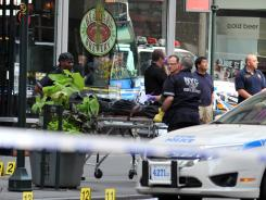 Investigators remove the body of the alleged shooter near the Empire State Building on Friday in New York.