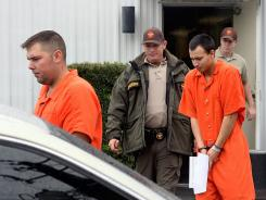 In this Dec. 12, 2011, photo, U.S. Army Sgt. Anthony Peden, 25, left, and Pvt. Isaac Aguigui, 19, are led away in handcuffs after appearing before a magistrate judge at the Long County Sheriff's Office in Ludowici, Ga.