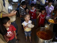 Syrian children, who fled their homes with their families due to fighting between the Syrian army and the rebels, wait to receive food at a border crossing.