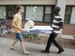 Karl Sadkowski, left, 18, talks with his roommate, Reggie Sackey-Addo, 17, as they carry a load of his belongings to their room at Grinnell College in Grinnell, Iowa on Saturday.