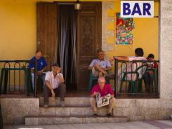 Residents sit, dejected, outside the only bar in Peleas de Abajo. The residents of this small village say they are ashamed of their status in Spain as the most indebted local government per capita in the country.