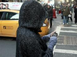 A pedestrian uses a phone by a crosswalk in New York.