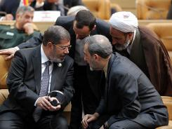 Egyptian President Mohammed Morsi, left, talks with Iranian officials during the Nonaligned Movement summit, in Tehran, Iran, on Thursday.