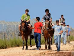 Campers Edden Bargai, 16, and Itay Barshai, 14, go for a ride this month at the Jordan River Village camp in Givat Avni, Israel.