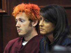 James Holmes, accused of killing 12 people in a shooting rampage in Aurora, Colo., movie theater, appears in Arapahoe County District Court with defense attorney Tamara Brady on July 23.