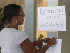 Democratic election judge Tinita Rivers adds fresh tape to a few signs outside Irving High School in the run-off election in Irving, Texas.