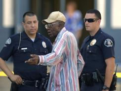 Preston Carter, 100, talks with police officers after his car allegedly went onto a sidewalk and plowed into a group of parents and children outside a South Los Angeles elementary school, Wednesday.