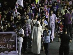 Residents carrying national flags march in Malkiya, Bahrain on Aug. 28.