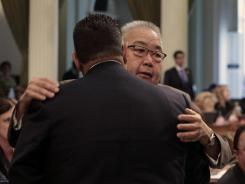 California Assemblyman Warren Furutani, D-Lakewood, right, receives a congratulatory hug from Assembly Speaker John Perez, D-Los Angeles, after his pension reform bill was approved Friday.