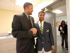 Jalen Rose Leadership Academy co-founder Jalen Rose greets student Brendyne Shelton, 15, in the office of the Detroit charter school.