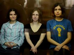"From left, members of the all-girl punk band ""Pussy Riot"" Yekaterina Samutsevich, Maria Alyokhina and Nadezhda Tolokonnikova sit in a glass-walled cage during a court hearing in Moscow on Aug. 17."