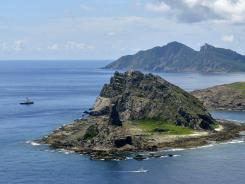 A survey ship, left, chartered by Tokyo city officials sails around tiny islands in the East China Sea on Sunday.