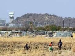 Young boys walk towards their home at the Lonmin Platinum Mine near Rustenburg, South Africa, Aug. 31.