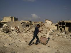 A Syrian man pushes a door away from the rubble of houses destroyed in a government airstrike, in the Syrian town of Azaz, on the outskirts of Aleppo, Aug. 31.