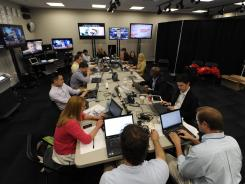 RNC employees monitor news and interviews at the NASCAR Hall of Fame building in downtown Charlotte Monday.