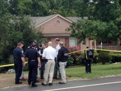 Police gather near the site where three people were killed in the Nashville suburb of Bellevue, Tenn.