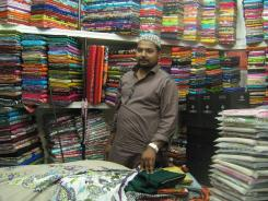Danish Arif is shown at at his fabric stall in Karachi's Mehran Bazaar.