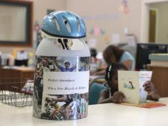 A bicycle helmet tops the container where students with a month's worth of perfect attendance can enter their names in a raffle to win the helmet and bicycle at the Maeola R. Beitzel Elementary School in Sacramento, Calif.