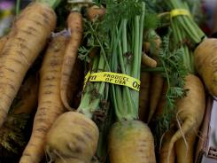 A farmers market offers organic carrots. A study finds no significant difference in vitamin content between organic and conventional veggies.