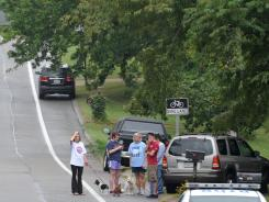 Neighbors gather near the site where three people were killed in the Nashville suburb of Bellevue, Tenn.