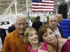 Former president Bill Clinton poses for photographs with attendees at a July green car event in Horn Lake, Miss.