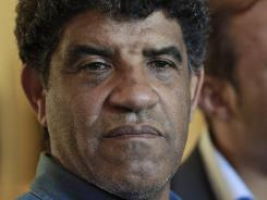 Abdullah al-Senoussi, head of Libyan intelligence, speaks to the press as gunfire erupts in Tripoli, Libya.