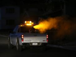 Contra Costa County Mosquito and Vector Control technicians drive a truck through an area sprayed with an insecticide Aug. 23 in Brentwood, Calif.