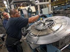 In Des Plaines, Ill.: A worker removes a coil of steel for manufacturing band saw blades last month.