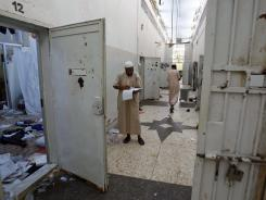 In this Saturday, Aug. 27, 2011, photo, Libyans search for documents inside Abu Salim prison, Libya's most notorious prison of Gadhafi's regime and the scene of a 1996 massacre of prisoners, in Tripoli, Libya.