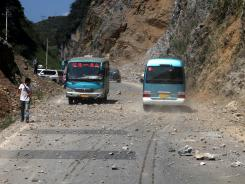 Two buses make their way across a road full of fallen rocks after a series of earthquakes hit the area near Zhaotong municipality at the border of southwest China's Yunnan and Guizhou province on Friday.