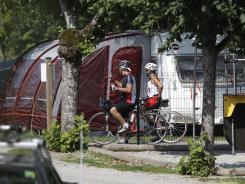 Cyclists look at the trailer where the slain British family was vacationing in a campsite of Saint Jorioz, near Annecy, France, on Friday.